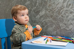 Child sitting at a table drawing Stock Images