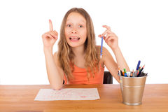 Child sitting at a table found an idea to draw. Isolated on a white background Royalty Free Stock Image