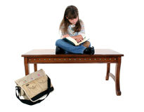 Child Sitting on Table Reading Book Stock Images