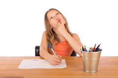 Child sitting at a table trying to make a drawing. Child sitting at a wooden table trying to make a drawing. Isolated on a white background Royalty Free Stock Photography