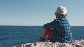 Child sitting on the top of the mountain and watching sea waves