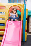 Child sitting on top of a slide Stock Photo