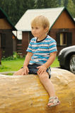 Child sitting on trunk Royalty Free Stock Photos