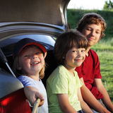 Child sitting in the trunk of a car on nature. Three cheerful child sitting in the trunk of a car on nature Stock Images