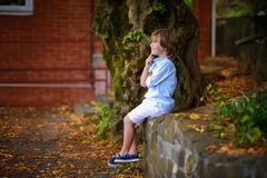 Child sitting under big tree Stock Images