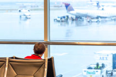 Child sitting and watching out a window in airport Stock Photography