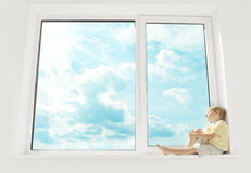 Child sitting on window, enjoying sunshine Royalty Free Stock Photos