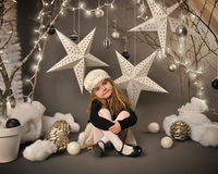 Child Sitting in Winter Tree Star Scene. A little girl is sitting in a winter wonderland setup with trees, hanging stars and Christmas lights around the royalty free stock photos