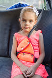 A child of six sitting in the back seat of car and strapped in using a restraint device Royalty Free Stock Photo