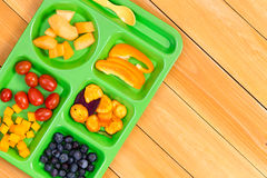 Child size lunch tray with fruit on wooden table Royalty Free Stock Photos