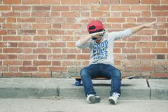 Child with skateboard in the street. Child with a skateboard and sunglasses in the street royalty free stock image