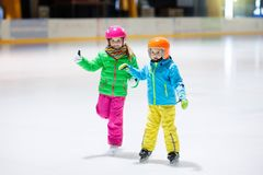 Child skating on indoor ice rink. Kids skate. Active family sport during winter vacation and cold season. Little girl and boy in colorful wear training or royalty free stock photos