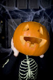 Child in a skeleton costume at a Hallowe'en party, holding a pumpkin with a carved face Stock Images