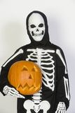 Child In Skeleton Costume Holding Jack-O-Lantern. Portrait of a kid dressed in skeleton costume holding Jack-O-Lantern isolated over white background Stock Images