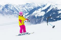 Child on ski lift. Kids skiing stock photo