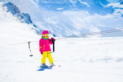 Child on ski lift in snow sport school in winter mountains. Child on a button ski lift going uphill in the mountains on a sunny snowy day. Kids in winter sport royalty free stock image