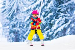 Child on ski lift in snow sport school in winter mountains. Child on a button ski lift going uphill in the mountains on a sunny snowy day. Kids in winter sport stock photography