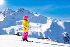 Ski and snow fun. Kids skiing. Child winter sport. Child skiing in mountains. Active toddler kid with safety helmet, goggles and poles. Ski race for young royalty free stock images