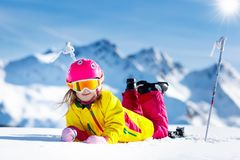 Ski and snow fun. Kids skiing. Child winter sport. Child skiing in mountains. Active toddler kid with safety helmet, goggles and poles. Ski race for young royalty free stock image