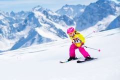 Ski and snow fun. Kids skiing. Child winter sport. Child skiing in mountains. Active toddler kid with safety helmet, goggles and poles. Ski race for young stock photo