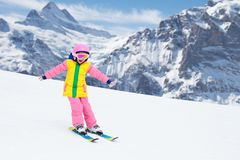 Child skiing in the mountains. Kid in ski school. Winter sport for kids. Family Christmas vacation in the Alps. Children learn. Downhill skiing. Alpine ski royalty free stock photo