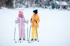 Child skiing in the mountains. Winter sport for kids. Little girls skiing in the mountains together. Winter sport for kids stock images