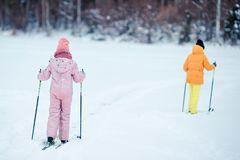 Child skiing in the mountains. Winter sport for kids. Little girls skiing in the mountains together. Winter sport for kids stock photo