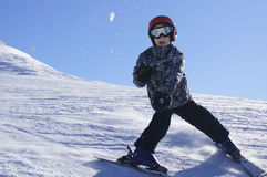 Child skiing and throwing snowball Royalty Free Stock Images