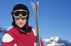 Child with skis, helmet and goggles in the skiing slope Royalty Free Stock Image