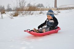 Child on sled. Riding down a small hill Stock Photography
