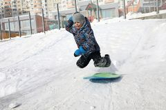 Child sled ride. On snow hill in winter Stock Photos