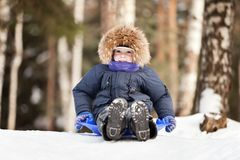 Child sled on snow hill. Little smiling boy sled tobogganing on winter snow hill Royalty Free Stock Photography