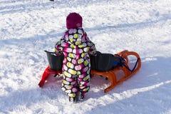 Child with sled on winter background. Child sledding Royalty Free Stock Photo