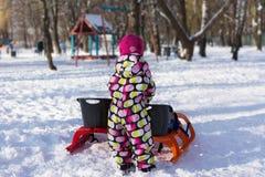 Child with sled on winter background. Child sledding Stock Image
