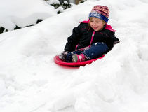 Child sledding down a hill Royalty Free Stock Photography