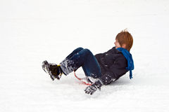 Child sledding down the hill Stock Photography