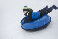 Child sledding down a hill on a snow tube Stock Photography