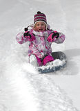 Child sledding down a snow hill Stock Photo