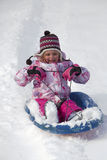 Child sledding down a snow hill Stock Photography