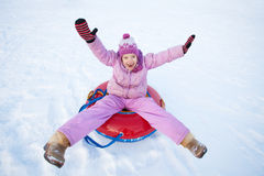 Child sledding in winter hill. Happy girl tobogganing Stock Image