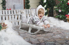 Child sledding in yard of winter snow Royalty Free Stock Images