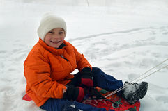 Child sledging in winter. Happy young boy sledging or tobogganing in the winter snow Stock Image