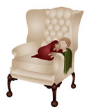 Child sleeping. A young child sleeping on a wing back chair Stock Images