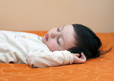 Child sleeping. Portrait of a sleeping child, boy or girl, lying on his back on an orange sheet Royalty Free Stock Photos