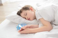 Child sleeping with alarm clock near his head Stock Photo