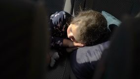 The child sleeping in the back seat of the car.