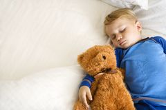 Child sleeping with bear. Stock Images
