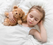 Child sleeping with a cute teddy bear. Adorable child sleeping in her bedroom with a cute teddy bear, hand under her head royalty free stock photography