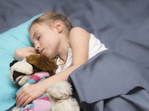 Child sleeping with her a favorite toy Royalty Free Stock Photography
