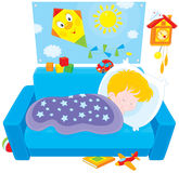 Child sleeping. Little boy sleeping on his couch in a kids bedroom with toys Stock Photos